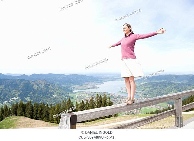 Mid adult woman balancing on fence, Wallberg, Tegernsee, Bavaria, Germany