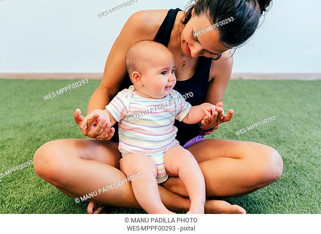 Young mother and baby exercising during mother child gymnastics