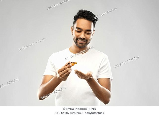 indian man applying grooming oil to his hand
