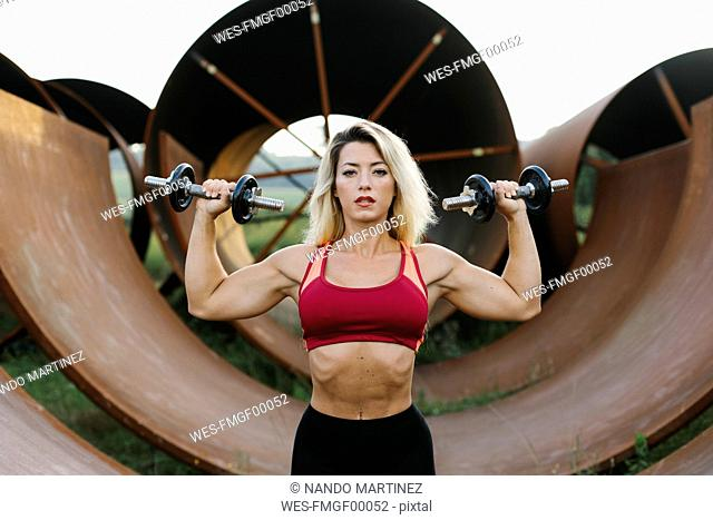 Athletic woman doing weight workout at industrial site