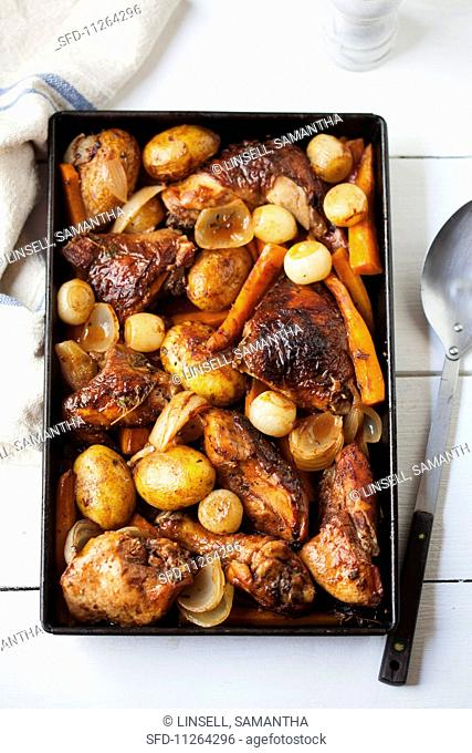 Roast chicken with potatoes, onions and carrots