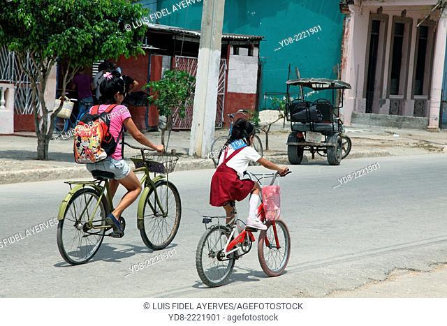 Mother and daughter riding bike in Moron, Ciego de Avila, Cuba