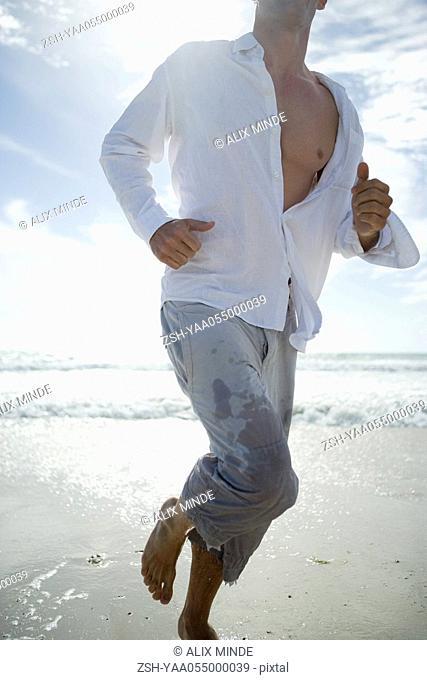 Man running on beach, neck down