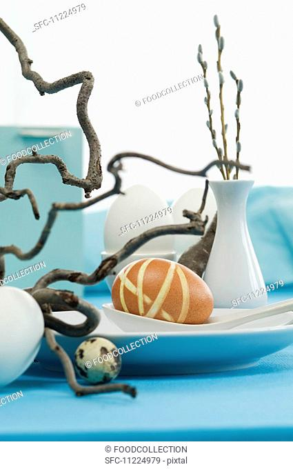 An Easter table decoration with eggs and corkscrew willow
