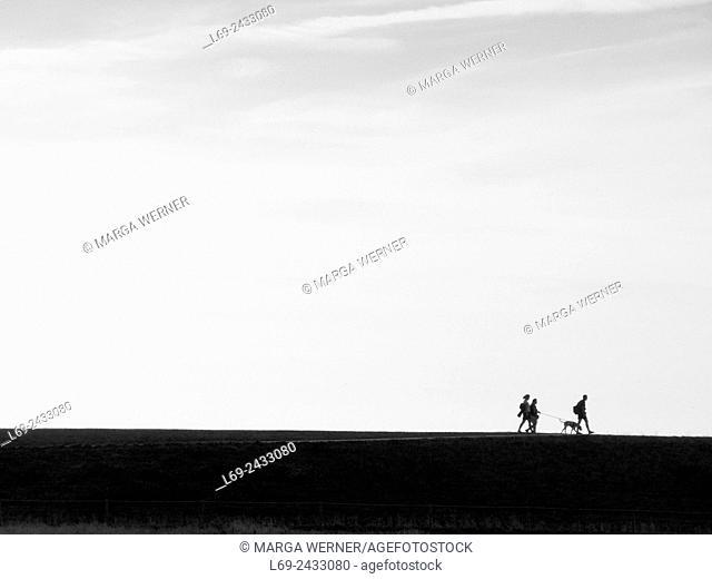 People and dog walking on a dyke of island Neuwerk, Elbe estuary, North Sea, Hamburg, Germany