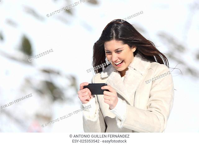 happy woman playing games in a smart phone on winter holidays with a snowy mountain in the background