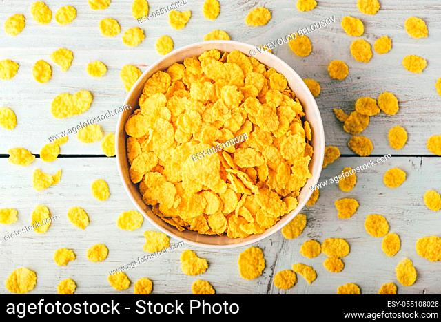 White bowl of corn flakes on a wooden surface