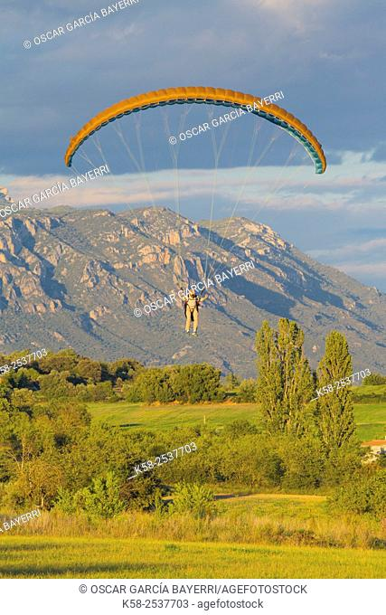 Paragliders flying in the pre-Pyrenees on the Montsec with the population of Ager, Lleida, Catalonia