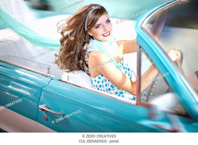 Woman with windblown hair driving vintage convertible