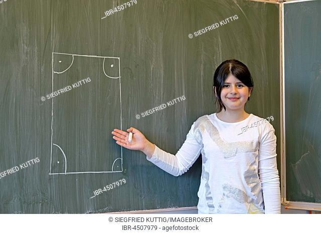 Girl at blackboard, drawn rectangle, elementary school, Germany