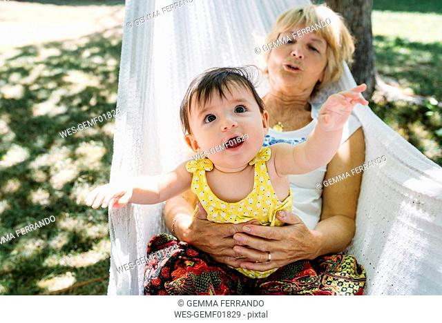 Spain, Grandma and baby relaxing in a hammock in the garden in the summer