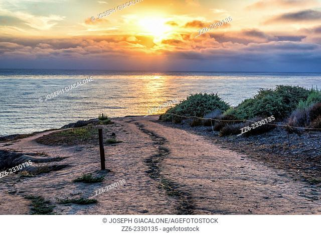 The Sun setting over the Pacific Ocean. View from hiking trail. Sunset Cliffs Natural Park, San Diego, California, United States