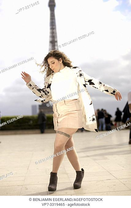 woman dancing outdoors in public in city next to tourist sight Eiffel Tower, at Espl. du Trocadéro, in Paris, France