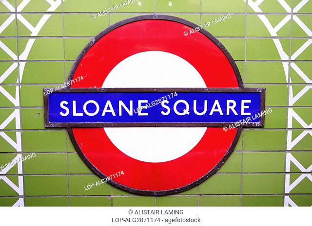 England, London, Sloane Square. Sloane Square Underground sign on a tiled wall inside the tube station