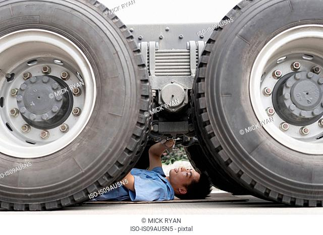 Male factory worker inspecting underneath truck in crane factory, China