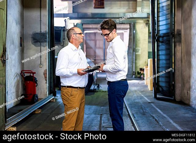 Two businessmen having a meeting in a factory hall