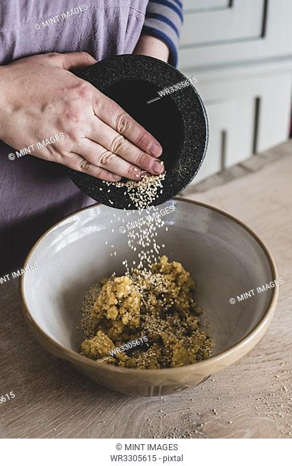 High angle close up of person adding sesame seeds to dough in a mixing bowl