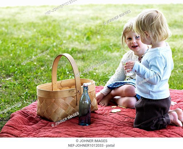 Two girls sitting on picnic blanket