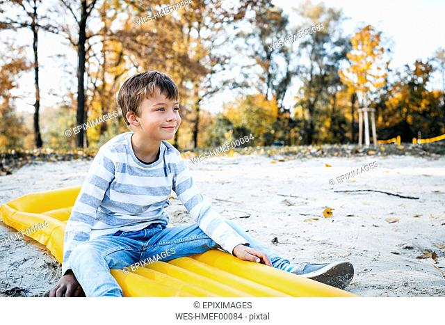 Content little boy sitting on yellow airbed on the beach in autumn