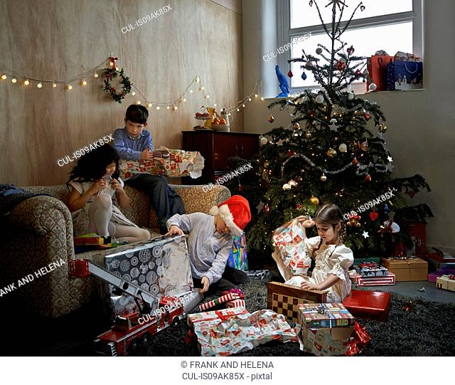 Sisters and brothers opening christmas gifts in sitting room