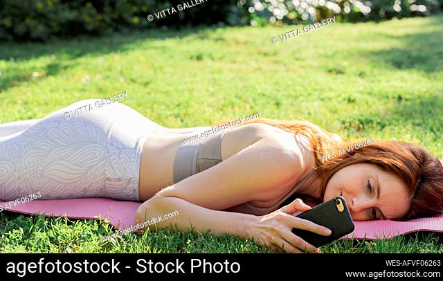 Young woman lying on a mat in grass checking cell phone