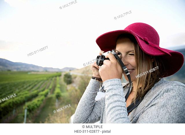 Woman wearing hat photographing with camera in vineyard