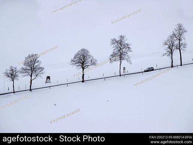 12 February 2020, Saxony, Rehefeld-Zaunhaus: A car drives on a narrow road over a snowy mountain in the Erzgebirge. A thin layer of snow attracts holidaymakers...