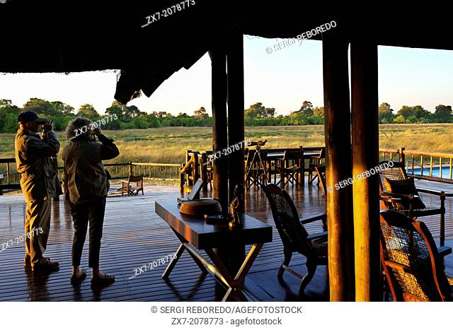A couple of tourists on the porch outside the camp Khwai River Lodge by Orient Express in Botswana, within the Moremi Game Reserve Wild