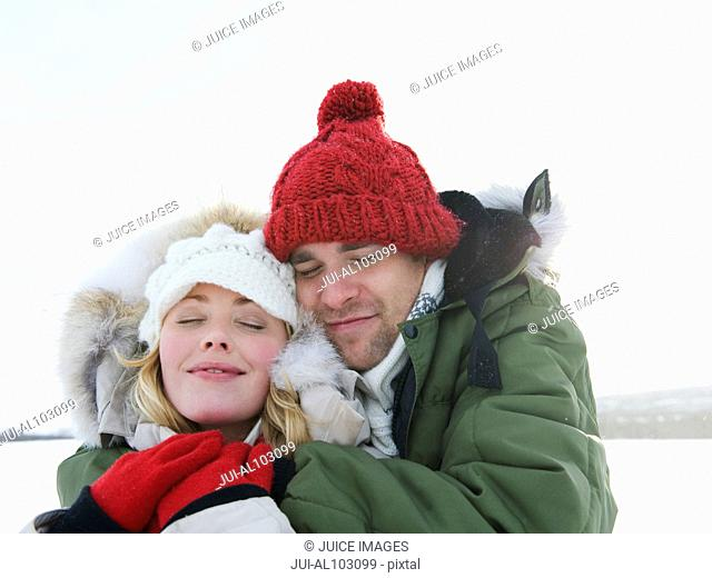 A young couple embracing to keep warm in the snow