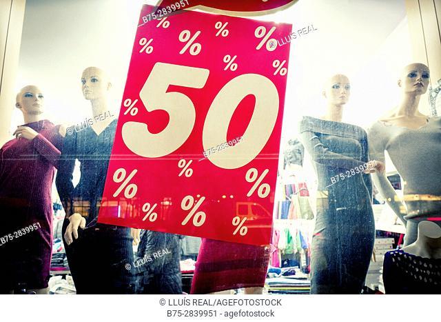 Primer plano de un escaparate de una tienda de moda con maniquís femeninos y un cartel grande de 50. Londres, West End, UK, Europa