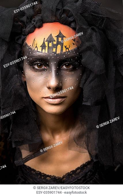 Halloween devil's bride. Portrait of young woman in dark artistic image with scary makeup, veil and terrible picture on her forehead