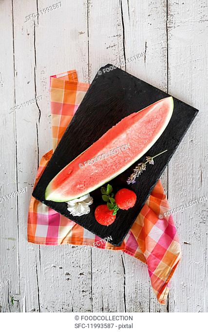 Fresh watermelon with mint and rosemary on a wooden table