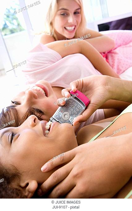 Three teenage girls 15-17 lying on bed, talking on mobile phones, smiling, close-up