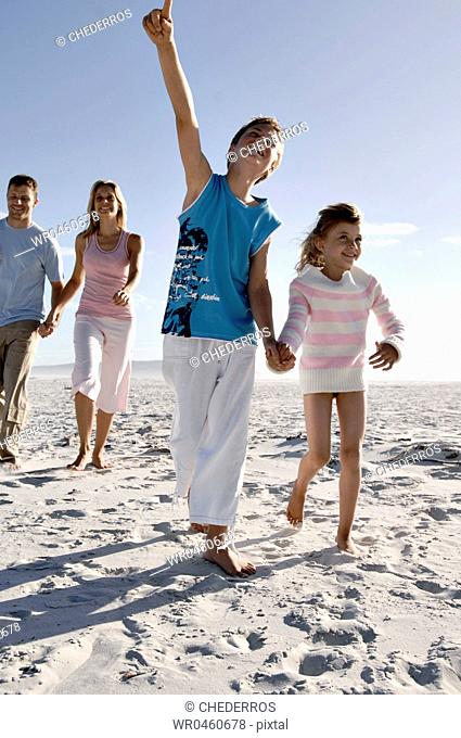 Mid adult couple with their two children running on the beach