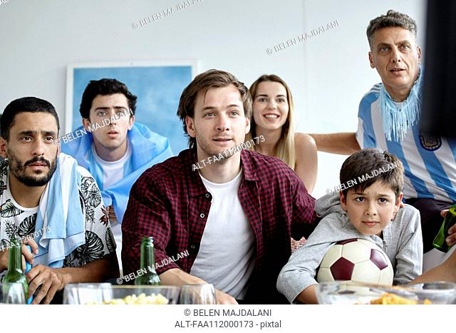 Argentinian football fans watching match on TV at home