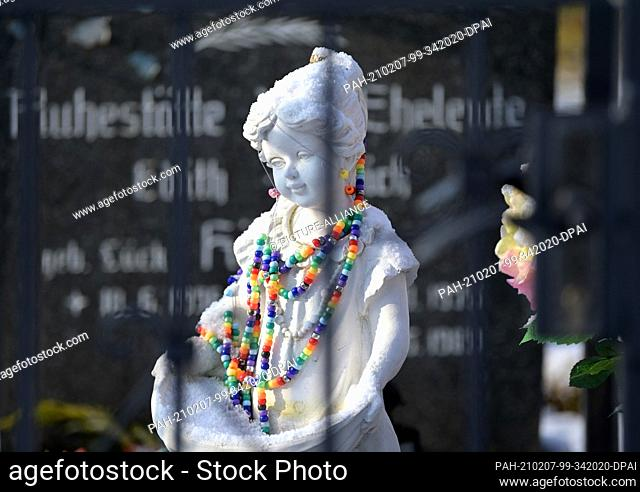 26 January 2021, Brandenburg, Birkholz: A white figure decorated with colourful beads stands in front of a grave in the church graveyard in the Bernau district...