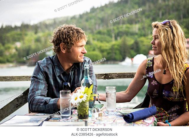 A couple in their 30's dining at the Saltry Restaurant in Halibut Cove, Kachemak Bay, Southcentral Alaska