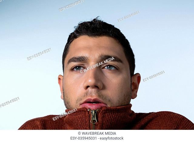 Scared man standing against white background