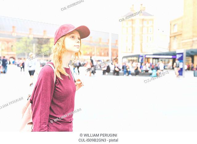 Portrait of woman wearing baseball cap looking away, London, UK