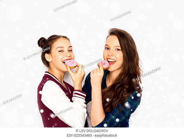winter, christmas, people, holidays and fast food concept - happy smiling pretty teenage girls or friends with donuts eating and having fun over gray background...