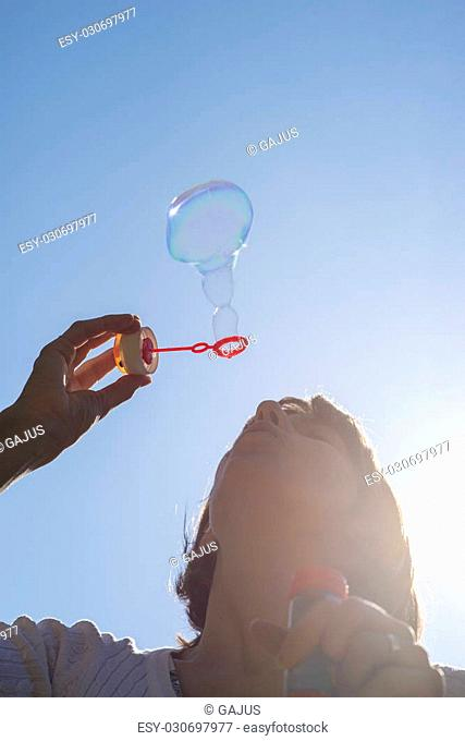 Closeup of young woman blowing soap bubbles under clear blue sky