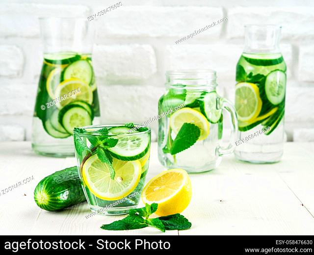 Infused detox water with cucumber, lemon and mint in different glass bottles on white table. Diet, healthy eating, weight loss concept. Copy space