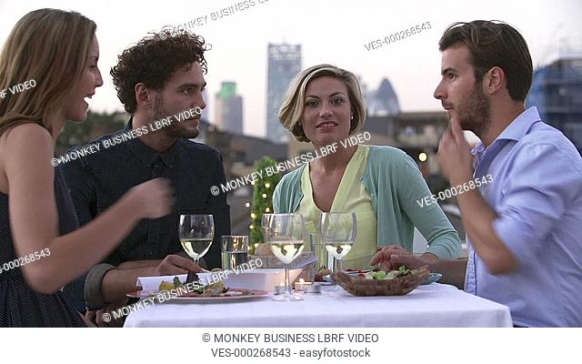 Group of friends propose toast as they enjoy evening meal on rooftop terrace.Shot on Sony FS700 in PAL format at a frame rate of 25fps