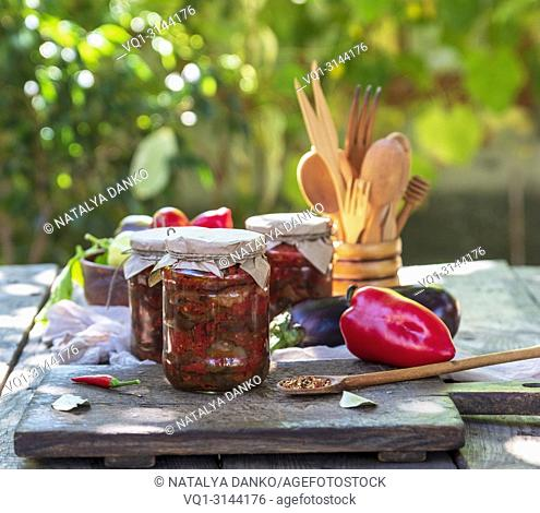 canned eggplant with vegetables on a brown wooden board, close up