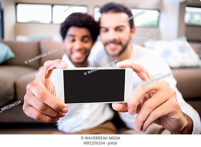 Happy gay couple taking selfie