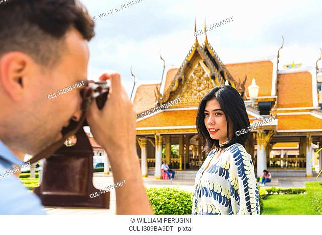 Young male tourist photographing girlfriend outside temple, Bangkok, Thailand