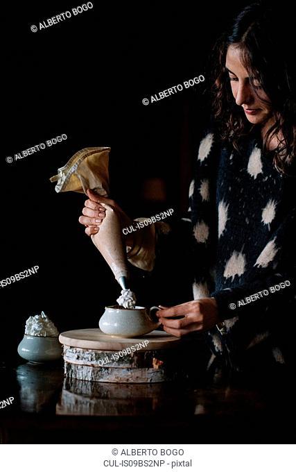 Young woman piping cream into bowl using piping bag