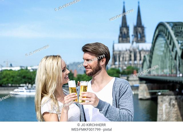 Germany, Cologne, happy young couple toasting with Koelsch glasses in front of Rhine River
