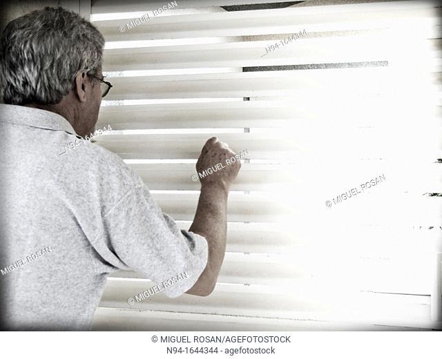 Senior man peering through the bars of the window