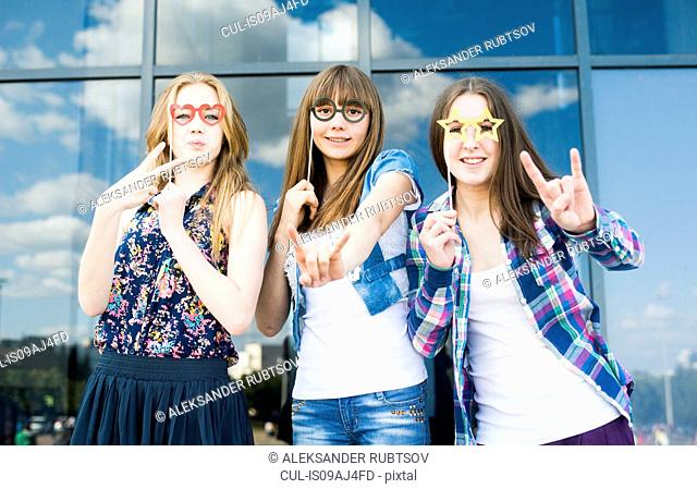 Portrait of three young women with eyeglasses costume masks and making hand gestures